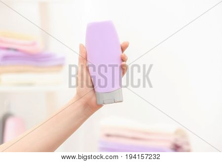 Hand of woman with bottle of cosmetic product in bathroom