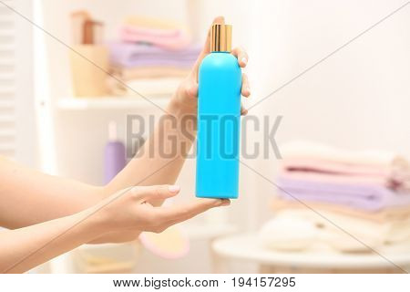 Hands of woman with bottle of cosmetic product in bathroom