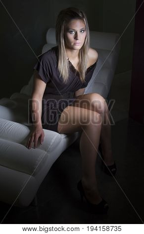 A  youngwoman is waiting on a couch