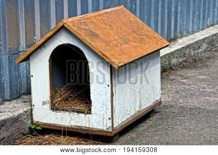 An empty doghouse of plywood near an iron fence