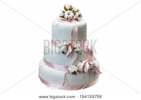 White three-tiered cake with cotton and pink ribbon isolated on white background