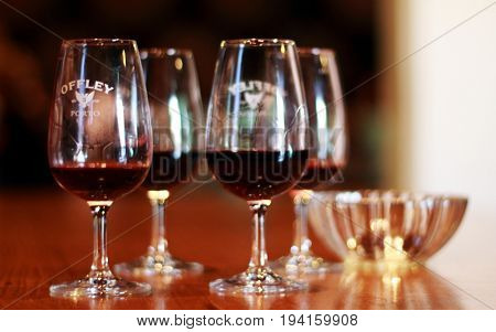 Porto, Portugal - May 9, 2014: Four grasses with port wine in the tasting room, city of Porto, Portugal.