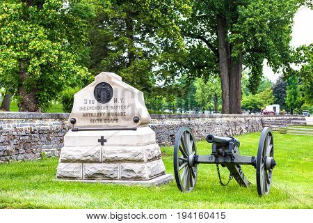 Gettysburg USA - May 24 2017: Gettysburg National Cemetery battlefield park with many grave stones and sites and cannon with sign