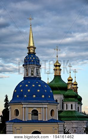 Green domes of Vydubitsky monastery in Kiev on the beautiful sky background. The plane fly near the dome. Warm summer evening