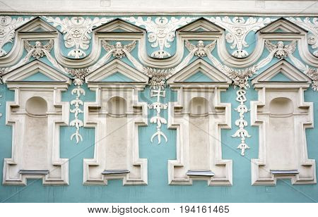 Figured white stucco on a blue background on the facade of an old building. Figures in the form of human faces, decoration of the facade