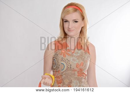 Fashion of the 1970s. Shoulder portrait of beautiful long-haired blonde in a short dress isolated on a white background. A model hairstyle, high heels, colorful accessories, orange short dress. Retro style.