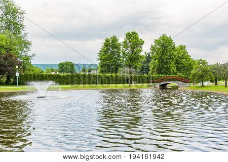 Harrisburg USA - May 24 2017: Italian Lake Park in Pennsylvania capital city with fountain bridge and path