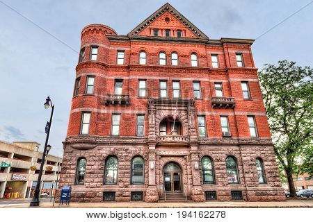 Wilkes-Barre USA - May 24 2017: City Hall in downtown city in Pennsylvania with brick building exterior sign and flag