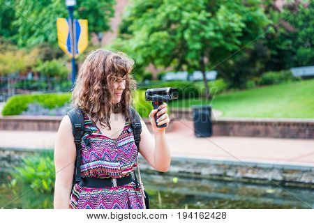 Young woman filming video using a camcorder with a grip during summer in park