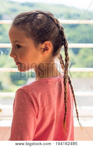 Girl with Dutch plaits looking out of window in profile. Young child with brown hair braided in a pink top