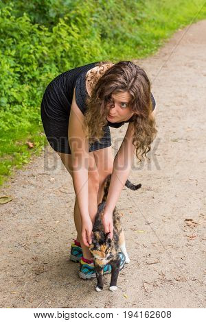 Young woman petting calico stray cat outside on trail path