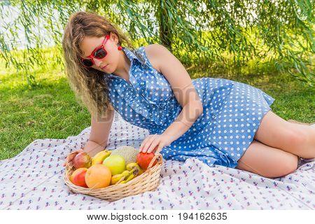 Young woman in red sunglasses lying down during picnic with fruit basket near Potomac River in Washington DC