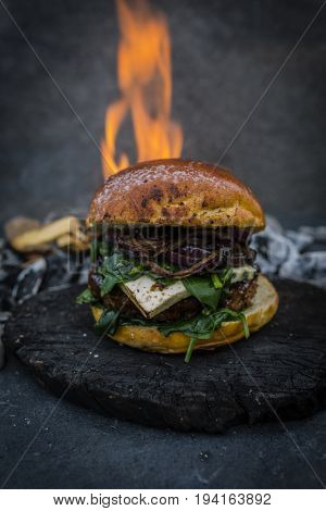 Tasty smoked grilled and glazed beef burger with lettuce, cheese and bacon served with french fries on wooden table with copyspace, flame and smoke mesquite timber wood in background.