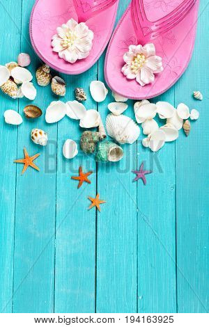 Pink flip flops and seashells on blue wooden background