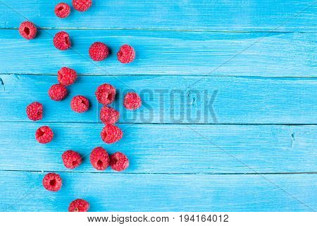 Fresh raspberries on a blue rustic wooden table