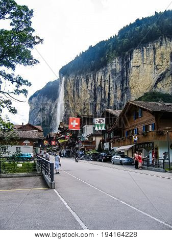 Interlaken Switzerland - August 12 2008: Village with people walking and tall waterfall on cliff