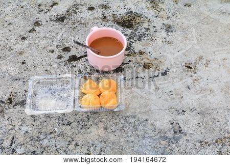 coffee cup pink plastic and cream puffs in box on the Cement floor old with copy space