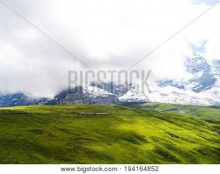 Swiss train during summer with alpine landscape in mountains in Interlaken with cloudy foggy mist