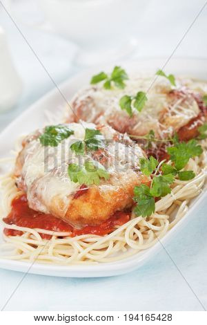 Italian parmesan chicken with melted cheese and tomato sauce served over spaghetti pasta
