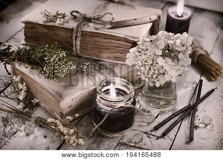 Toned still life with black candles, old book and flowers on planks. Alternative medicine, old pharmaceutic and homeopathic concept. Mystic and occult still life, vintage medical background