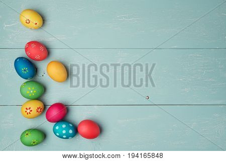 multicolored easter eggs on vintage painted wooden background with craquelure