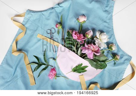 Composition of beautiful peonies and apron on white background