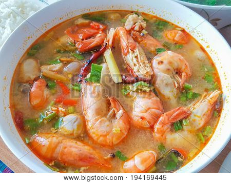Homemade Tom Yum Koong (Thai Language) is prawn and lemon grass soup with mushrooms the famous delicious Thai food.