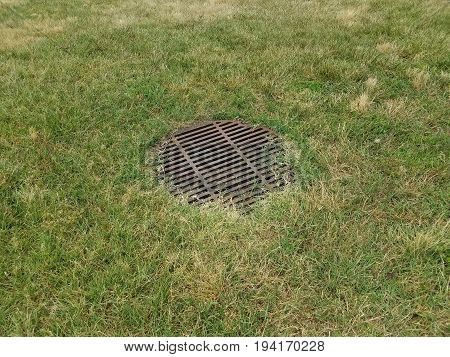 metal grate of iron bars on drain in the green grass