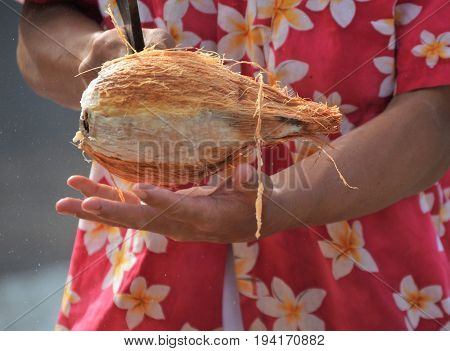 coconut being held and chopped with cleaver