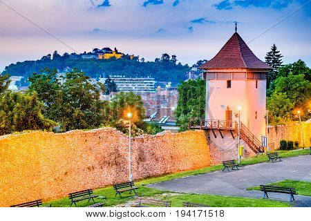 Brasov Romania - Twilight image with medieval city walled fortifications Black Church and the Citadel.