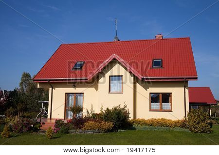 Single family house in yellow color against blue sky