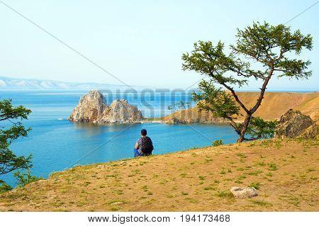 A woman backpacker looks at the Shamanka Rock, Cape Burhan on Olkhon Island. Lake Baikal, Siberia, Russia.