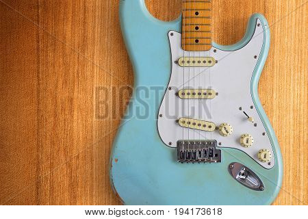 A light blue electric guitar against a warm colored wood background.