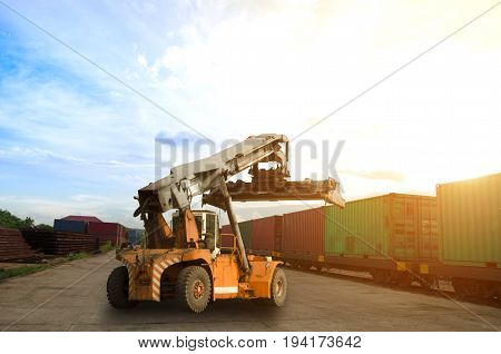 stacker and container train freight for import export concept in sunset background