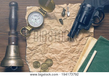 Adventurer western reward page treasure hunt or travel concept. Compass revolver gun money diary book train conductor bell pencil and blank crumpled brown page paper on wooden table.