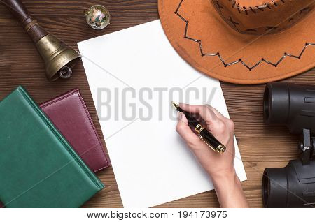 Adventurer treasure hunt travel concept or education mockup background. Hand with pen globe books binoculars train conductor bell (teacher bell) hat and blank paper page on table.