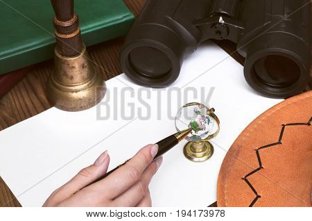 Female hand points to glass globe by pen binoculars books train conductor bell (teacher bell) money pen hat and blank page paper. Adventurer traveler concept or education concept.