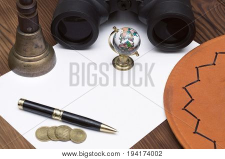 Adventurer treasure hunt traveler concept or education mockup background. Globe binoculars train conductor bell (teacher bell) money pen cowboy hat and blank page paper on table.