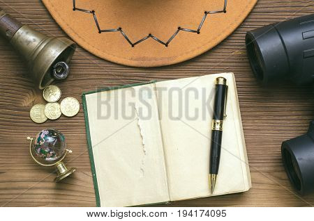 Adventurer treasure hunt traveler concept or education mockup background. Globe binoculars train conductor bell (teacher bell) money pen cowboy hat and open diary book on table.