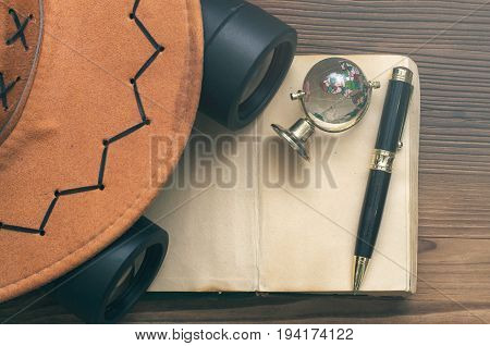 Adventurer treasure hunt travel concept or education mockup background. Globe book binoculars pen hat and blank page book on table.
