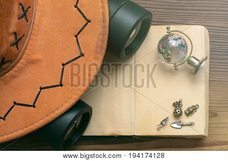 Adventurer treasure hunt travel concept or education mockup background. Globe book binoculars hat decoration chest and blank page book on table.