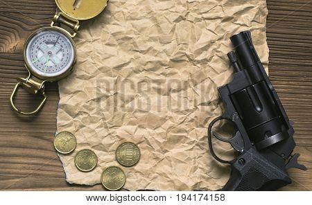 Adventurer western reward treasure hunt concept. Compass revolver gun money and blank crumpled brown page paper on wooden table.