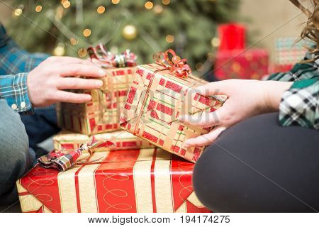 Close up on a young couple sitting on the floor as they exchange Christmas gifts