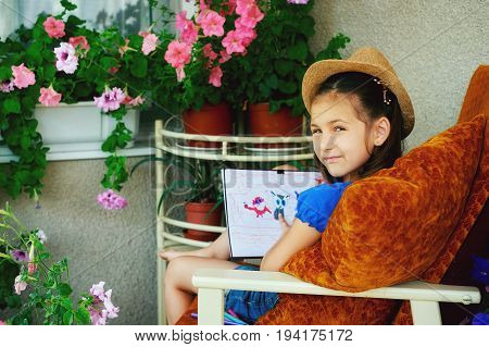 Little girl draws in the summer on the veranda with flowers