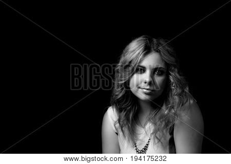 Black and white low key portrait of attractive long hair young woman looking forward and smiling.
