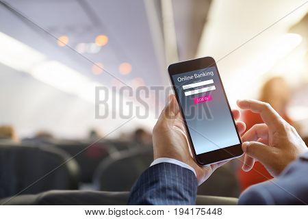 Business man with online bank application phone at the airplane. e-banking concept.