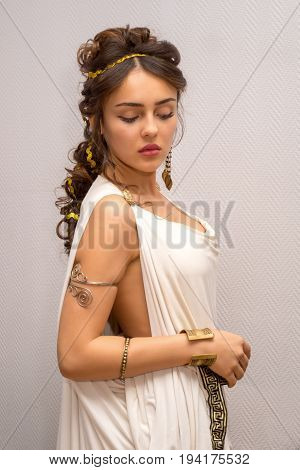 portrait of a beautiful graceful greek young woman in a traditional antique white tunic standing side and looking down
