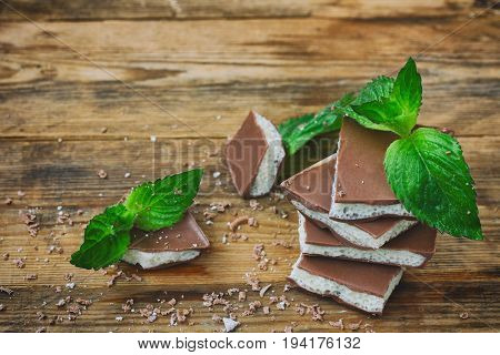 Milky porous white and dark chocolate with mint leaves and crumbs on a wooden table