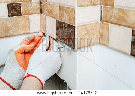 The tiler's hands are using plastic wedges to align tiles on the wall.