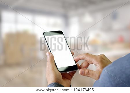Man using Smartphone with blurred office background. Blank screen smartphone for Graphic display montage.